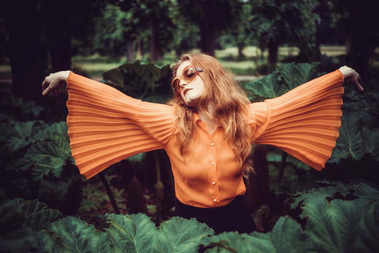 Young woman imitating a butterfly dressed orange Beautiful Woman Close-up Day Green Color Nature One Person Outdoors People Tree Young Adult Young Women