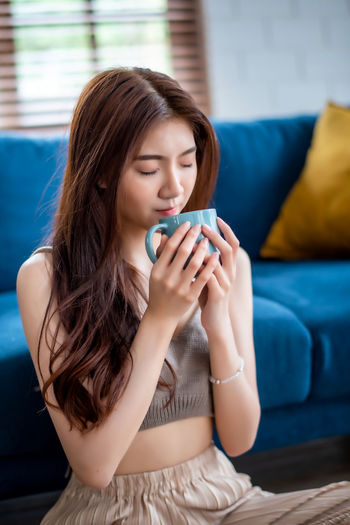 Beautiful young woman drinking coffee while sitting on sofa