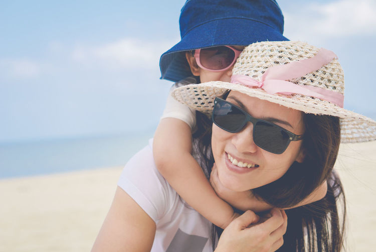 Close-up of smiling mother carrying daughter while standing at beach against sky