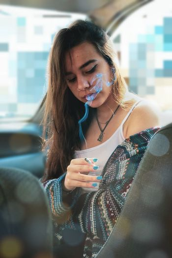 Fashionable Young Woman Smoking Cigarette While Sitting In Car