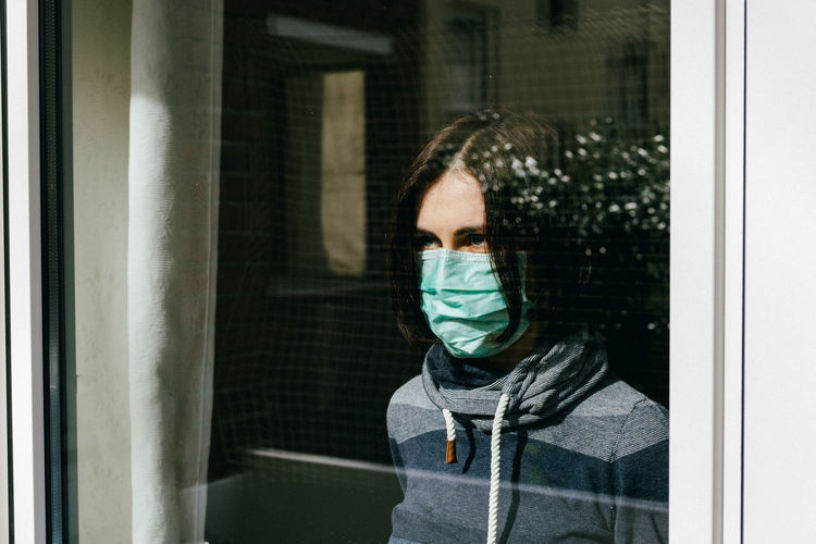 Woman with pollution mask looking away seen through window