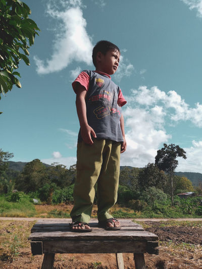 Full length of boy looking at camera against sky
