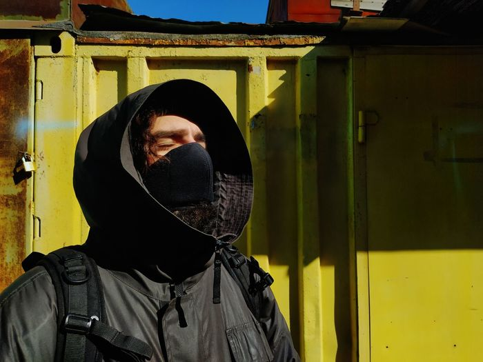 Man wearing hood and mask standing outdoors