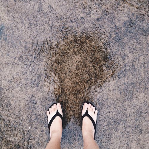Low Section Of Woman Wearing Slippers Standing On Wet Street