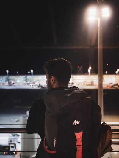 Rear view of man looking at illuminated city at night