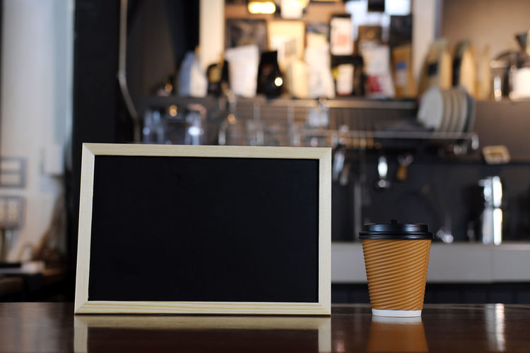 Close-Up Of Disposable Cup And Blackboard On Table