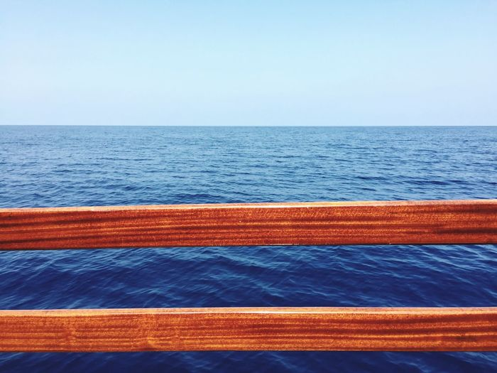 Wooden Railing Of Boat Against Seascape