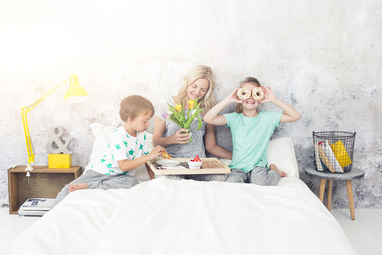 Mother with children having breakfast on bed