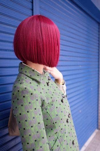 Redhead woman standing against store with shutters down