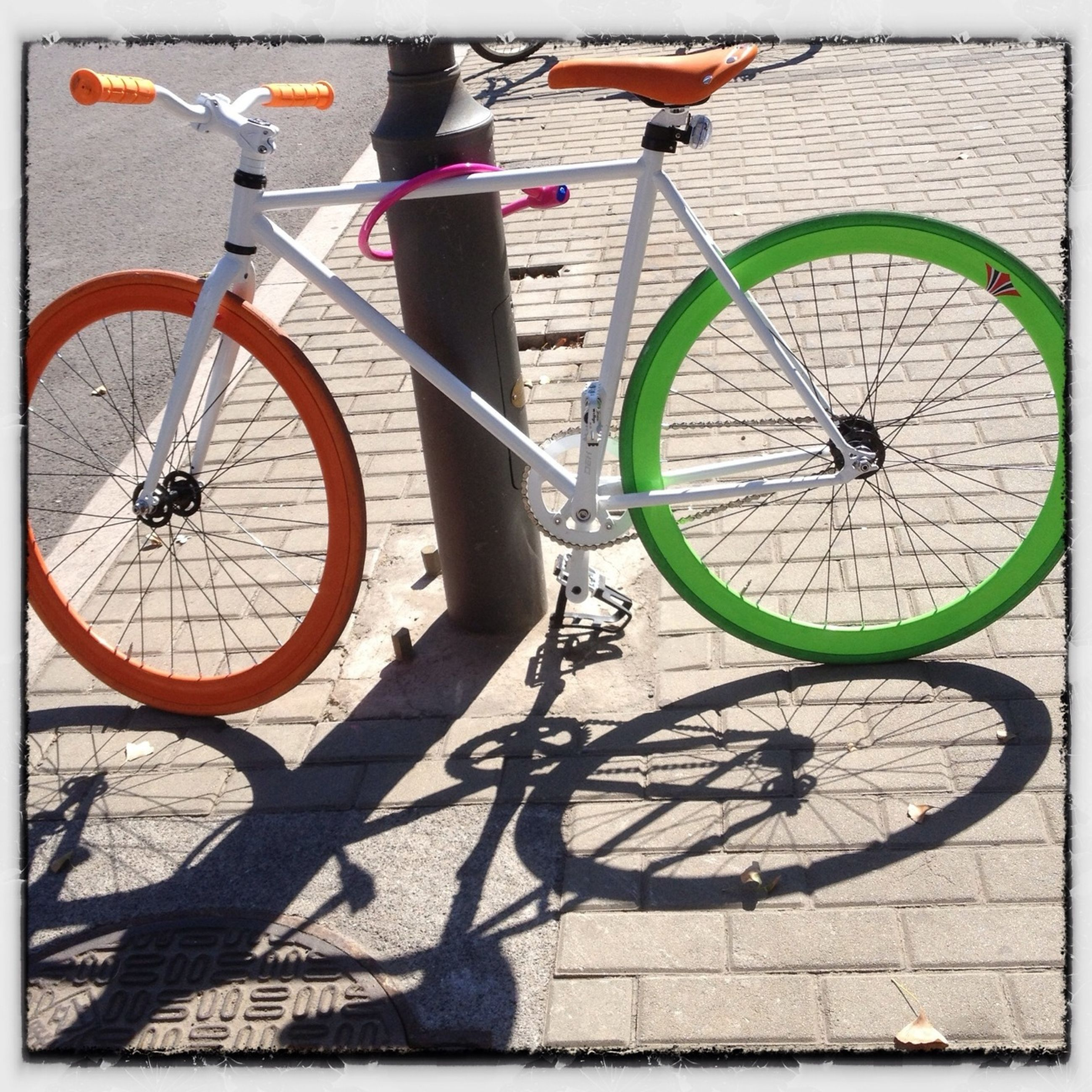 bicycle, transportation, mode of transport, transfer print, land vehicle, stationary, parked, parking, auto post production filter, wheel, street, day, shadow, cycling, sunlight, outdoors, cycle, travel, pole, built structure