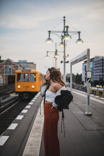 Side View Of Young Woman Standing On Platform At Railroad Station