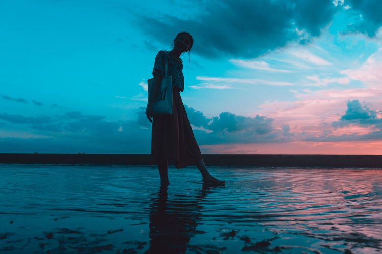 Man standing by swimming pool against sea during sunset