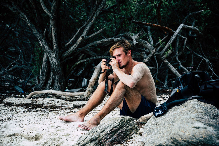 Full length of shirtless man sitting on rock in forest