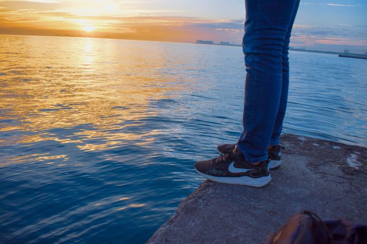Low Section Human Leg Human Body Part Body Part Water Sea Standing Shoe One Person Human Limb Adult Nature Beach Jeans