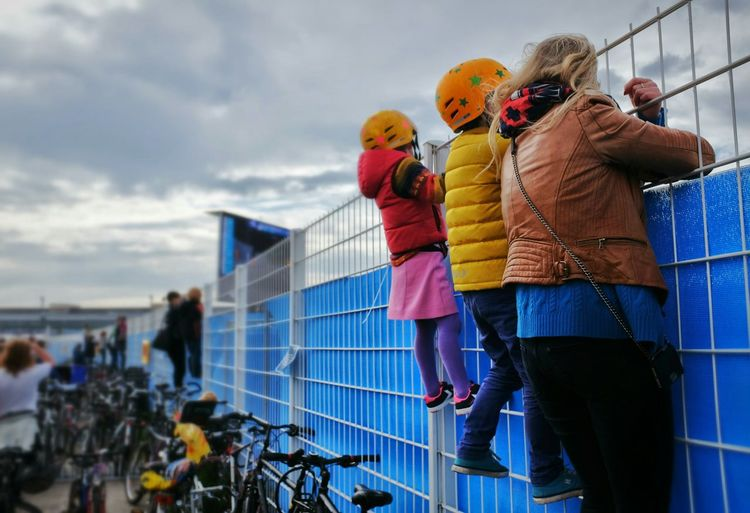 Spectators Climbing On Fence Against Cloudy Sky