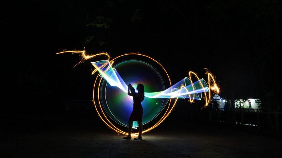 Light trails on ferris wheel at night