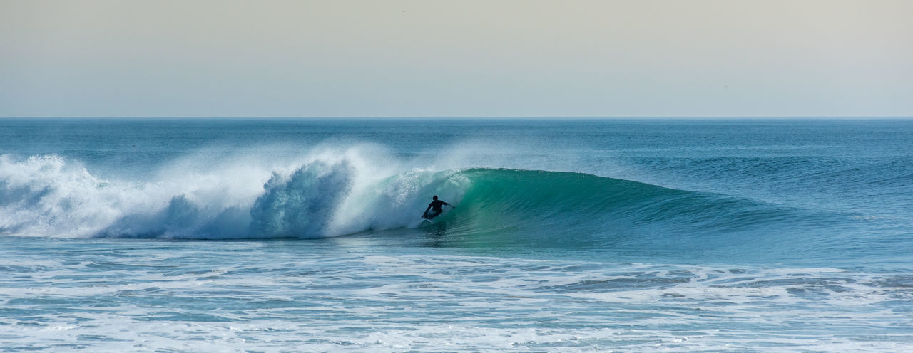 Panoramic view of person surfing in sea against clear sky