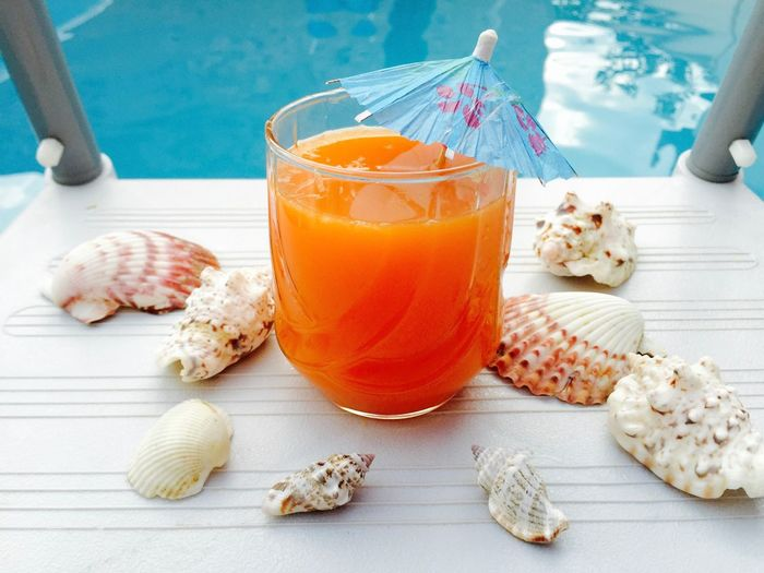 Glass of orange juice with blue umbrella and seashells near the blue pool water