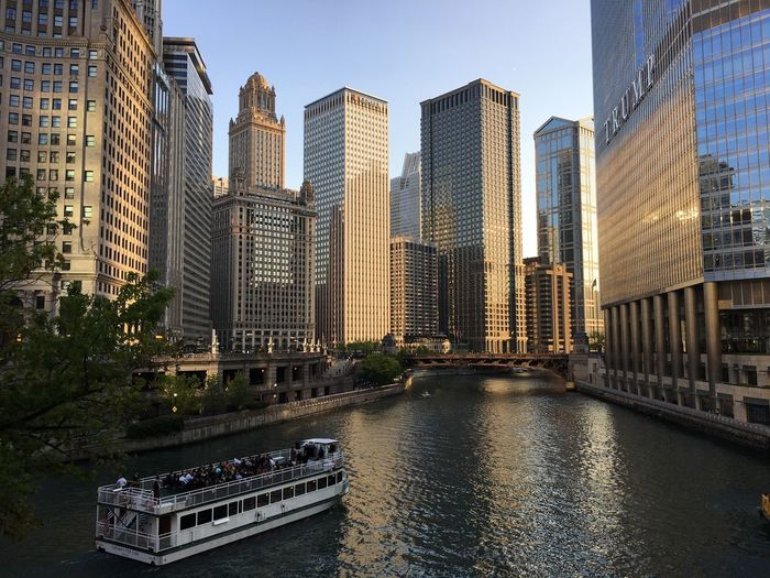 Chicago river at sunset with a boat Building Exterior Architecture Built Structure City Water Building Nautical Vessel Skyscraper Sky Waterfront Transportation River Mode Of Transportation Outdoors Cityscape Passenger Craft