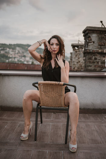 Portrait Of Mid Adult Woman Sitting On Chair Against Sky