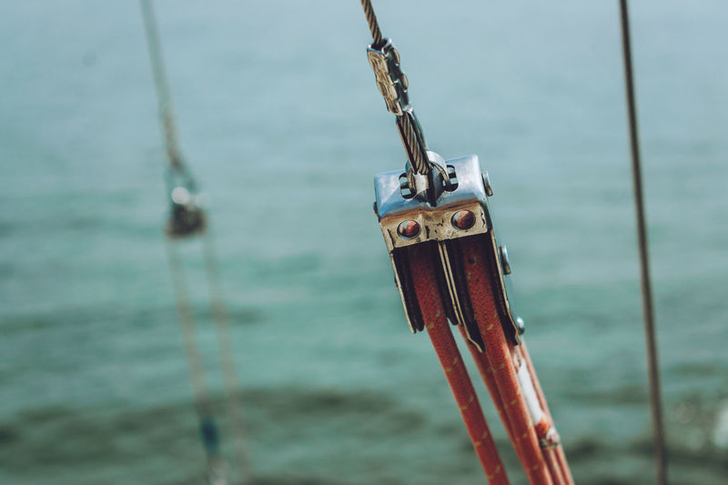 Close-up of rope tied with cable on pulley at sailboat