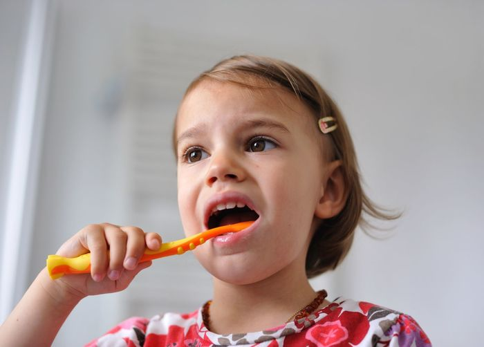 Close-up of girl brushing teeth against wall