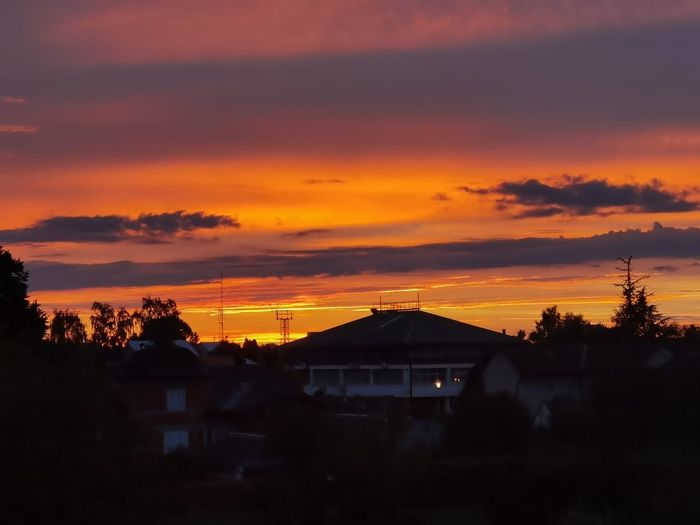 Silhouette houses and trees against dramatic sky during sunset
