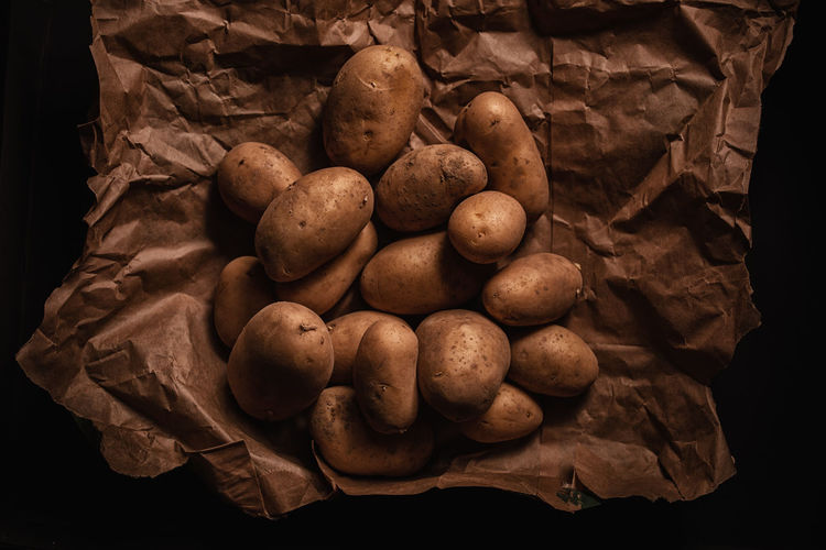 Wellbeing Potato Freshness Food Indoors  Healthy Eating No People Still Life Food And Drink Studio Shot Close-up Vegetable Brown Black Background Raw Food Large Group Of Objects Paper Root Vegetable Raw Potato High Angle View