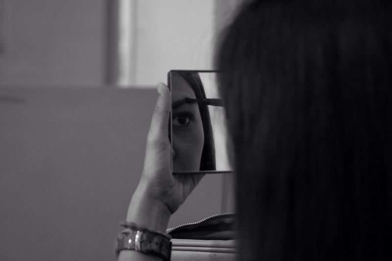 Cropped image of woman reflecting in mirror while applying eyebrow pencil