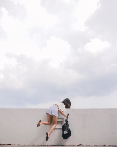 Woman Climbing On Wall Against Sky