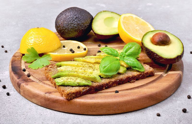 Delicious fresh avocado meal, bread and avocado fruit on a wooden cutting section of avocado and lemon, healthy eating or lifestyle theme with concrete background. Breakfast Dish Freshness Fruits And Vegetables Meal Toast Wood Avocado Bread Citrus Fruit Close-up Concrete Food Food And Drink Fresh Fruit Freshness Fruit Healthy Healthy Eating Healthy Food Healthy Lifestyle Indoors  Lemon No People SLICE