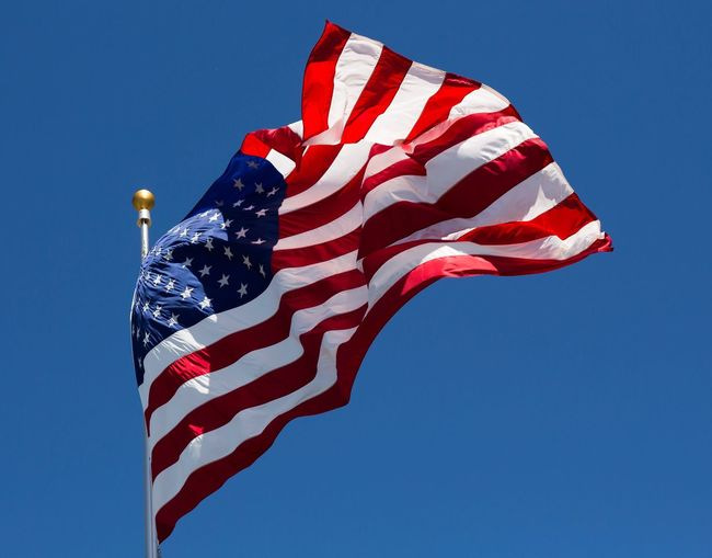 Low angle view of american flag against clear blue sky during sunny day