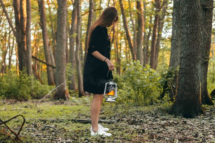Girl in black skirt with oil lamp walking on the forest at the evening. Awesome mood. Casual Clothing Day Forest Full Length Growth Hairstyle Land Leisure Activity Lifestyles Nature One Person Outdoors Plant Real People Shorts Tree Tree Trunk Trunk Women WoodLand Young Adult Young Women