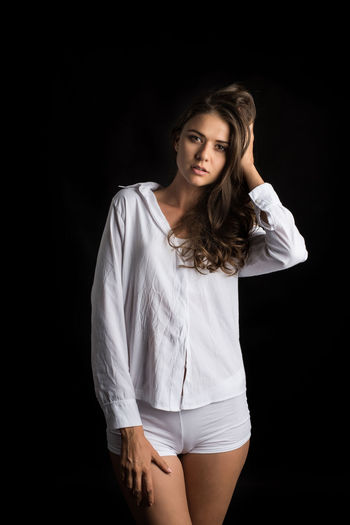 Young Adult Black Background Studio Shot Front View One Person Young Women Indoors  Looking At Camera Three Quarter Length Beauty Beautiful Woman Portrait Cut Out Standing Hairstyle Casual Clothing Long Hair Hair Fashion Contemplation