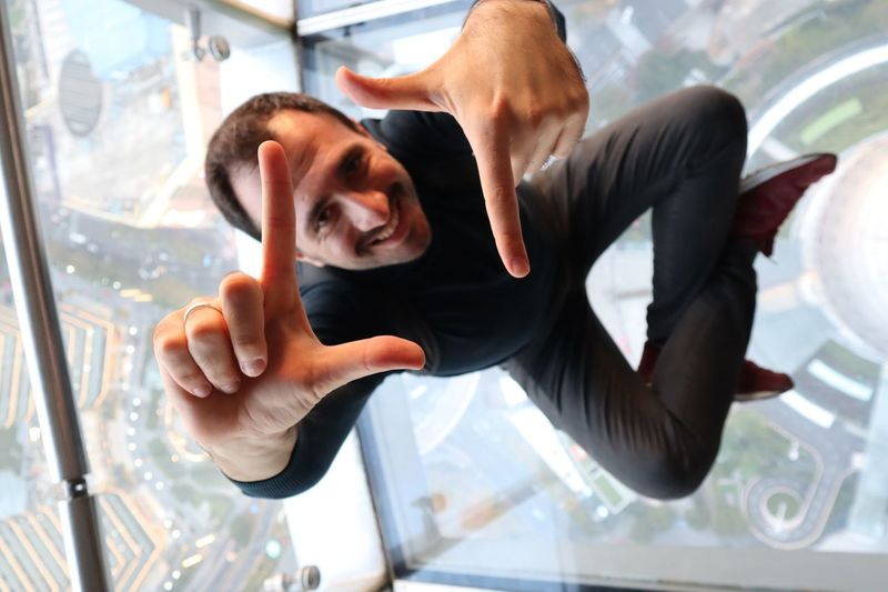 High Angle View Of Man Sitting On Glass Floor