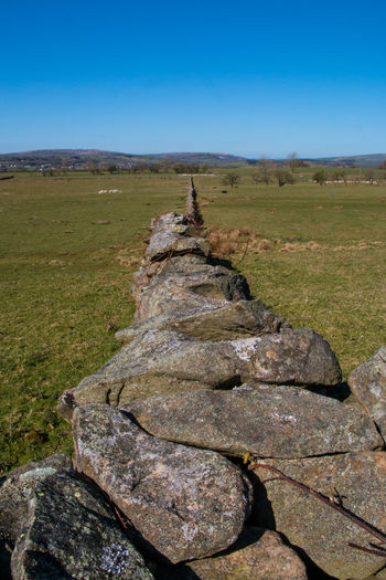 Scenic view of rocks on field against clear blue sky