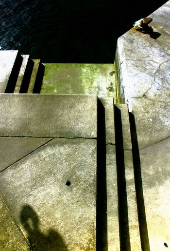 A Landing-Stage Architecture Built Structure Concrete Contrasts Geometric Shape Harbor Landing-stage Light And Dark Light And Shadow No People Outdoors Steps Up And Down Urban Geometry Water Weathered Wall