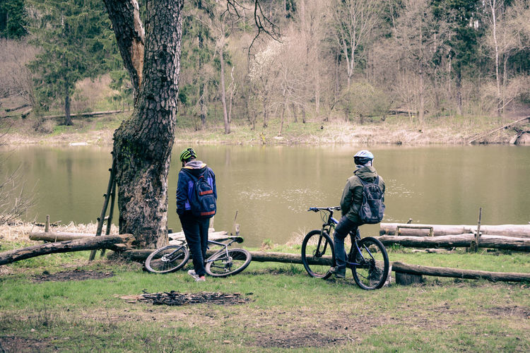 Rear view of men with bicycle by lake