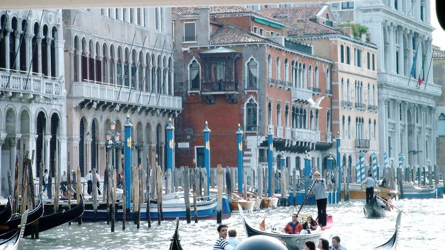 People in gondola on grand canal by buildings