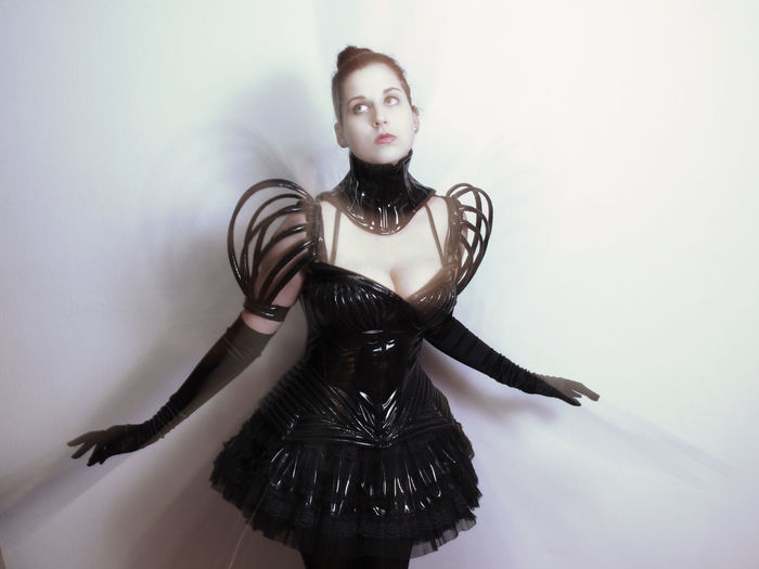 Young woman wearing costume standing against white wall