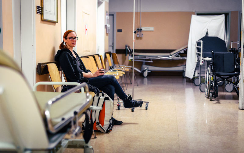 Mid adult women sitting on chair at hospital
