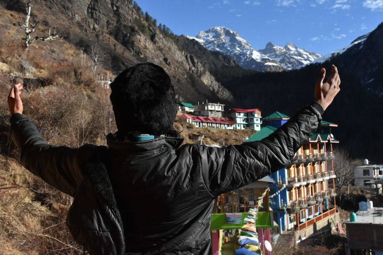 Rear view of man holding snowcapped mountains against sky