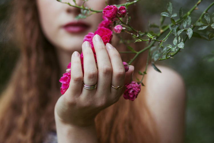 Close-up of woman hand on pink flowering plants