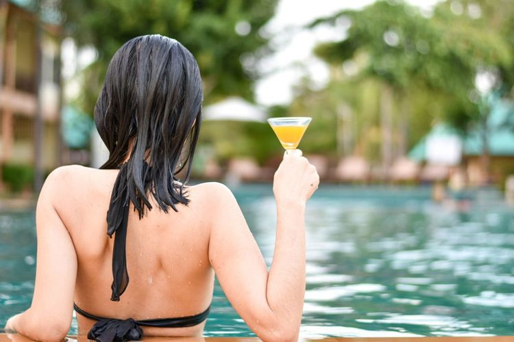 Rear view of woman holding drink while relaxing in swimming pool