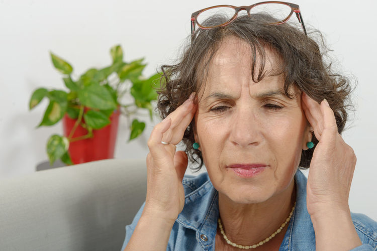 Mature woman with head in hands at home