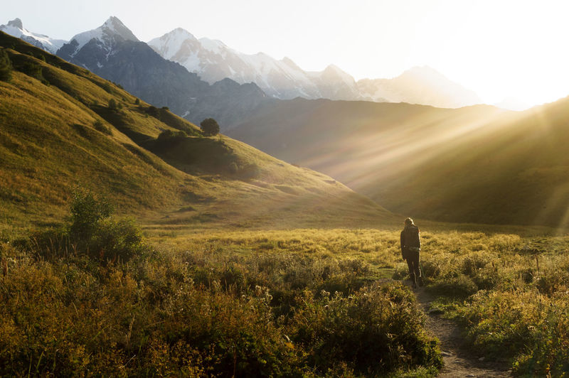 Walking to Ushguli from Mestia at dawn. Beauty In Nature Environment Grass Land Landscape Leisure Activity Lifestyles Men Mountain Mountain Range Nature Non-urban Scene One Person Outdoors Plant Real People Rear View Scenics - Nature Sky Tranquil Scene Tranquility My Best Travel Photo
