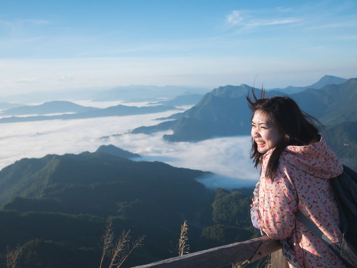 Smiling woman standing on mountain against sky