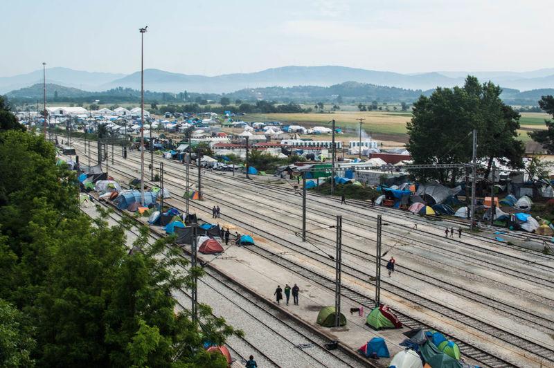 Railroad tracks amidst refugee camp tents