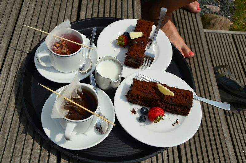 Close-Up Of Served Chocolate Cake Slice With Tea In Plate