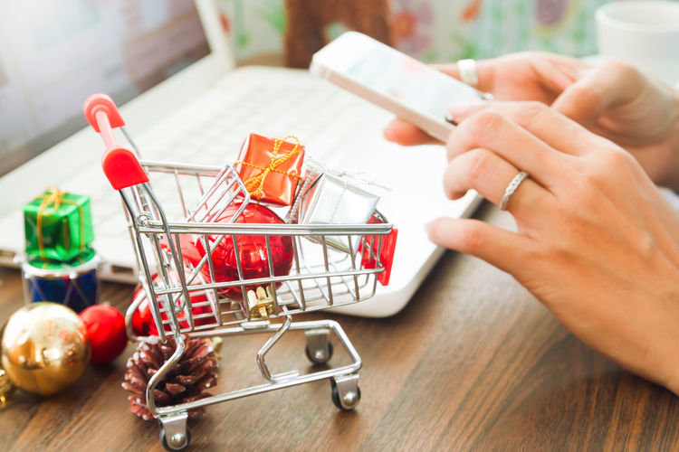 Cropped Image Of Woman Photographing Christmas Decoration In Shopping Cart